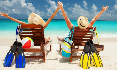 couple in beach chairs with arms in air