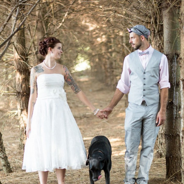 Bride and groom posing with dog