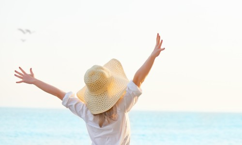 Woman on beach with arms in air