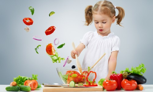 Young girl stirring salad