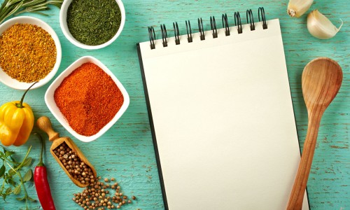 notepad surrounded by spices and spoon