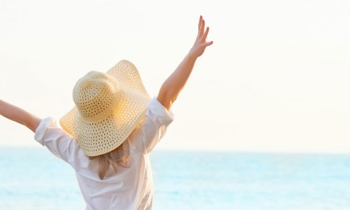 woman wearing sunhat throwing hands in air