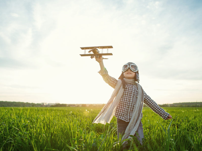 playful boy with toy plane