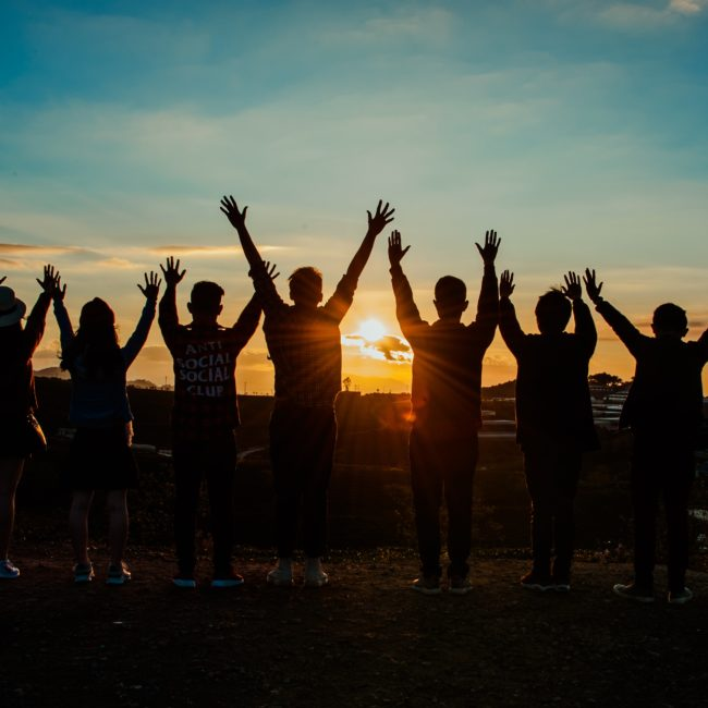 group with hands raised at sunset