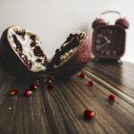 pomegranate and clock on table