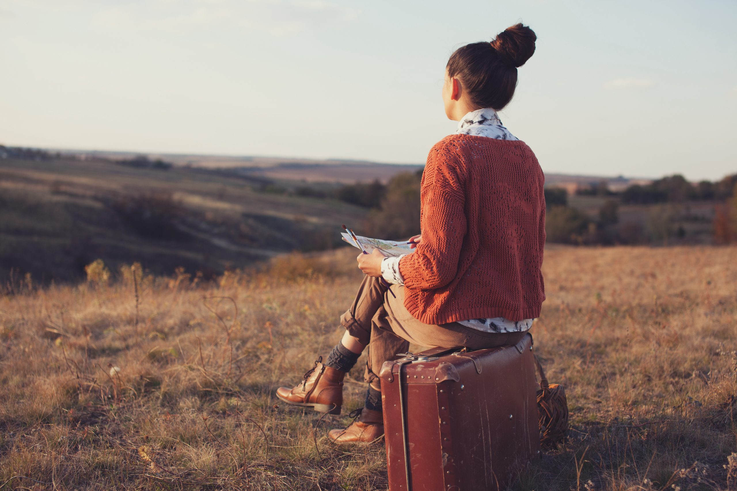 woman sitting on suitcase facing the unknown