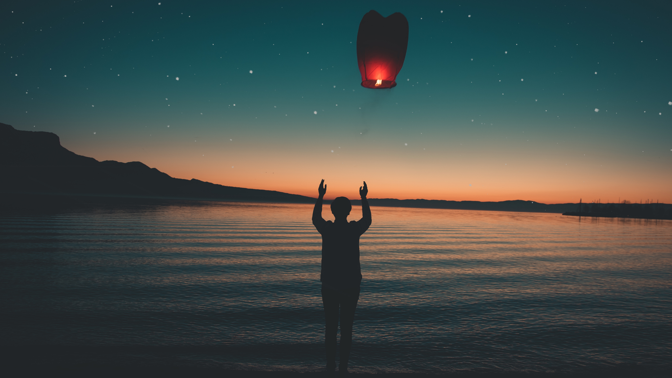 man letting a lit paper lantern into the sky at the ocean
