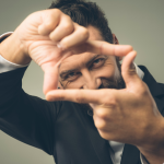 man creating frame in front of his face with his fingers to symbolize the concept of reframing