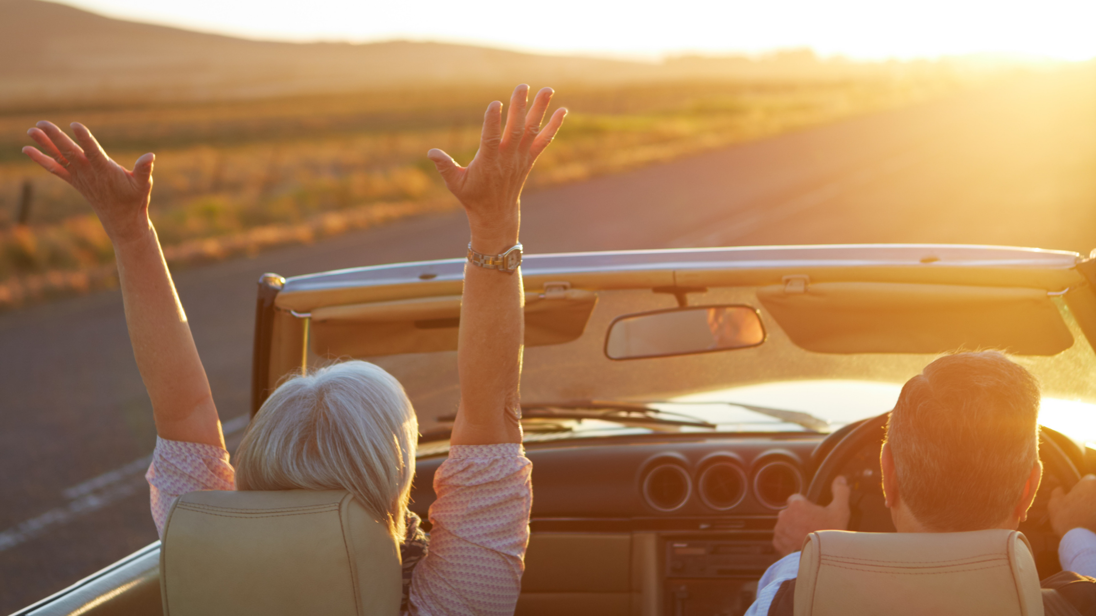 woman and man in a car enjoying the ride along a wide, open road into the sun